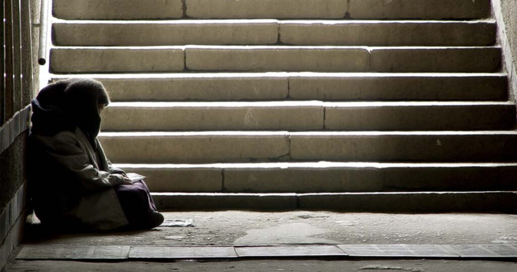 Homeless person next to stairs